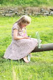 Little girl with a mobile phone on a swing. Barefoot little girl in a flowered dress holding a mobile phone on a swing Royalty Free Stock Images
