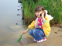 Little girl with a mobile telephone. Little girl on the riverside. Fun and mobile communication Stock Photo