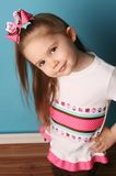 Little girl modeling hair bow and matching shirt. Cute young girl wearing a t shirt and matching hair bow, posing in studio with hands on hips stock photo