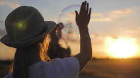 Little girl and mom blowing soap bubbles in wheat field at sunset time. Slow motion video.