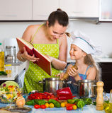 Little girl and mom with cookery book Royalty Free Stock Photo