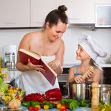 Little girl and mom with cookery book Stock Photography