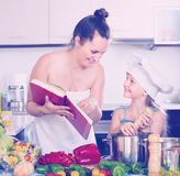 Little girl and mom with cookery book Stock Photos
