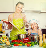 Little girl and mom with cookery book Royalty Free Stock Photos
