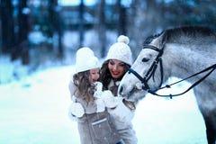 Little girl and mom feeding little horse pony winter. Stock Photos