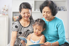 Little girl with mom and grandma reading book royalty free stock photos