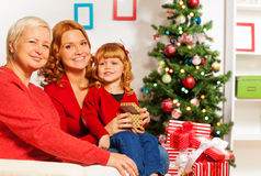 Little girl with mom and granny opening presents Stock Photo