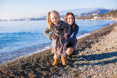 Little girl with mom having fun on the beach in a Royalty Free Stock Photography