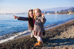 Little girl with mom having fun on the beach in a Stock Photos