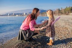 Little girl with mom having fun on the beach in a Stock Photography