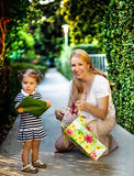 Little girl with mom holding present. Little girl is impatient to give present Royalty Free Stock Photos