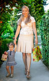 Little girl with mom holding present. Little girl is impatient to give present Royalty Free Stock Image