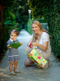 Little girl with mom holding present. Little girl is impatient to give present Royalty Free Stock Images