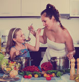 Little girl with mom at kitchen Royalty Free Stock Image