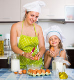 Little girl with mom at kitchen Royalty Free Stock Photos