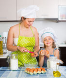 Little girl with mom at kitchen Stock Images