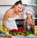 Little girl with mom at kitchen Stock Photography