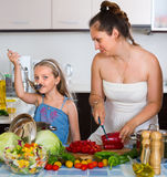 Little girl with mom at kitchen Stock Photo