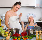 Little girl with mom at kitchen Royalty Free Stock Images