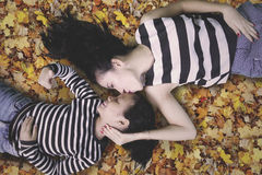 Little girl and mom lying on autumn leaves. Top view of a cute little girl lying with her mom on autumn leaves at park while showing thumb up at the camera Royalty Free Stock Image