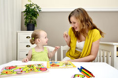 Little girl and mom playing. In a children puzzle Royalty Free Stock Images