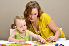 Little girl and mom playing. In a children puzzle Stock Photo