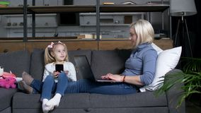 Little girl and mom spending time using devices. Preadolescent daughter with smart phone choosing game to play and asking for mother`s help. Reclining on cozy stock footage