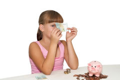 Little girl with money in hands  isolated. Little girl with money in hands and piggy bank on  table isolated Stock Image