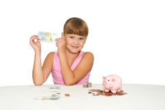 Little  girl with money in hands  isolated. Smiling little  girl with money in hands and piggy bank on table isolated Royalty Free Stock Photos