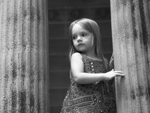 Little girl, moody portrait. Black and white portrait of little girl between two pillars with apprehensive look, shallow focus royalty free stock images
