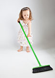 Little girl with mop. On gray background Royalty Free Stock Photography