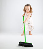 Little girl with mop. On gray background Royalty Free Stock Images