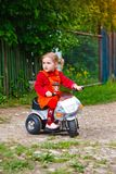 Little girl on the moped in the country Stock Image