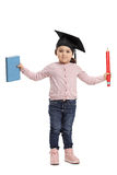 Little girl with mortarboard holding book and pencil Royalty Free Stock Photography