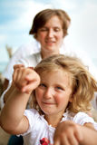 Little girl with mother. Blond girl with mother playing, girl looking to the camera stock photo