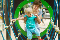 Little girl with mother at action-oriented playground Stock Photo