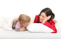Little girl with mother in bedding Royalty Free Stock Photos