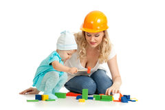 Little girl and mother with building blocks. And hard hat Royalty Free Stock Photo