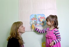 The little girl with mother considers drawings of vegetables Royalty Free Stock Image