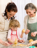 Little girl with mother cutting out cookies Stock Photos