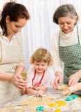 Little girl with mother cutting out cookies Royalty Free Stock Photography