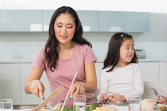 Little girl and mother eat food in kitchen. Little girl and mother eat food in the kitchen at home Royalty Free Stock Photo
