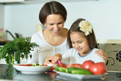 Little girl with mother eating Stock Photos