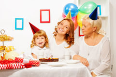 Little girl with mother and granny on birthday. Happy laughing family daughter mother and granny wearing party caps on the birthday table with cake and candles Stock Images