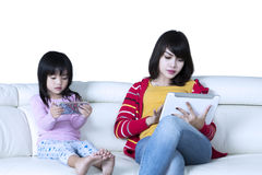 Little girl and mother holding gadgets Royalty Free Stock Images