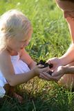 Little girl and mother holding a plant Royalty Free Stock Images