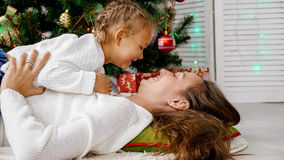 Little girl and mother hugging indoors with christmas tree on the background. Childhood, happiness, christmas, family and people concept - smiling little girl Royalty Free Stock Photography