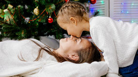Little girl and mother hugging indoors with christmas tree on the background. Childhood, happiness, christmas, family and people concept - smiling little girl Stock Image