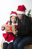 Little girl and Mother kissing and giving Xmas Present Royalty Free Stock Image