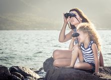 Little girl and mother looking far away with binoculars. Sitting on a rock near a sea stock photo